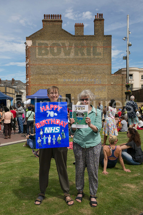 Two ladies celebrate the 70th anniversary of the NHS at Windrush Square during the 70th anniversary of the Empire Windrush arriving in England on the 23rd June 2018 in Brixton in the United Kingdom. Following the arrival of 492 passengers from the Caribbean on the 22 June 1948, it marked a seminal moment in Britain's history. (photo by Sam Mellish / In Pictures via Getty Images)