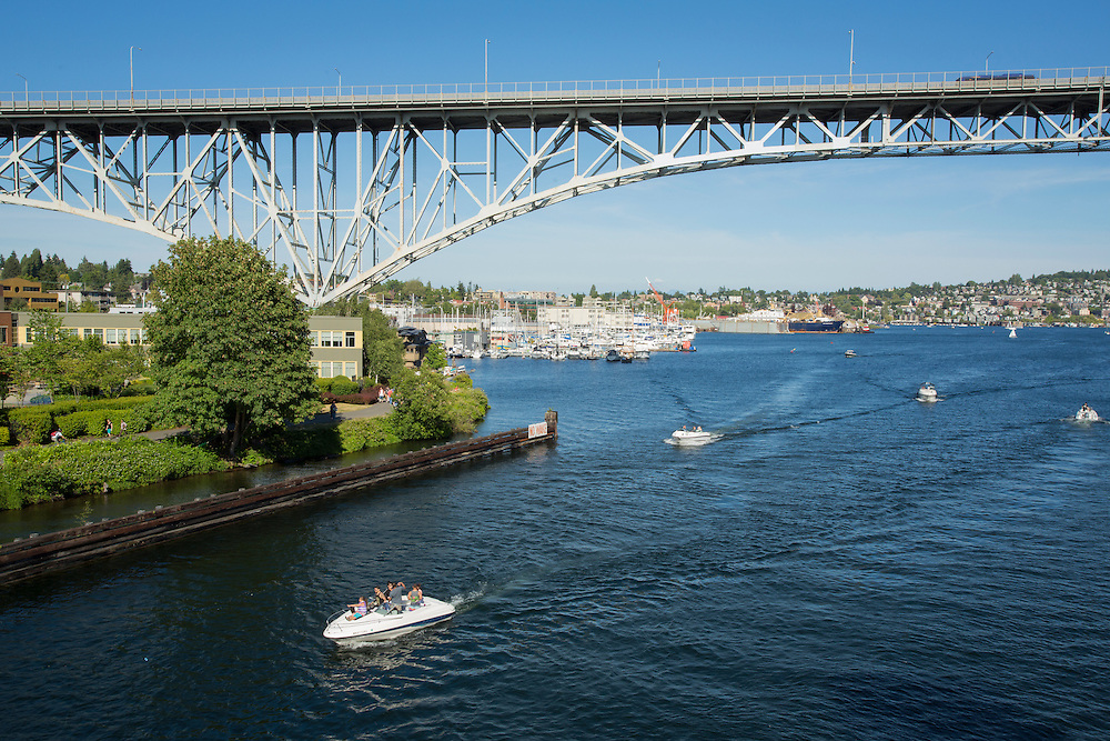 United States, Washington, Seattle. Motorboats heading west out of Lake Union into the Ship Canal, passing under the Aurora Avenue bridge.
