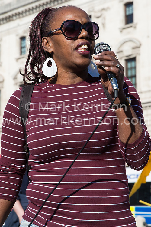 London, UK. 26th February, 2019. Ana, a cleaner from the Department for Business Energy and Industrial Strategy (BEIS), addresses mainly migrant striking outsourced workers belonging to the Independent Workers of Great Britain (IWGB), United Voices of the World (UVW) and Public and Commercial Services Union (PCS) trade unions working at the University of London (IWGB), Ministry of Justice (UVW) and Department for Business Energy and Industrial Strategy (PCS), together with representatives of the National Union of Rail, Maritime and Transport Workers (RMT) Regional Council, taking part in a 'Clean Up Outsourcing' demonstration to call for an end to the practice of outsourcing. The demonstration was organised to coincide with a significant High Court hearing of an application by the IWGB for judicial review of a decision by the Central Arbitration Committee (CAC) not to hear their application for trade union recognition for the purposes of collective bargaining with the University of London.
