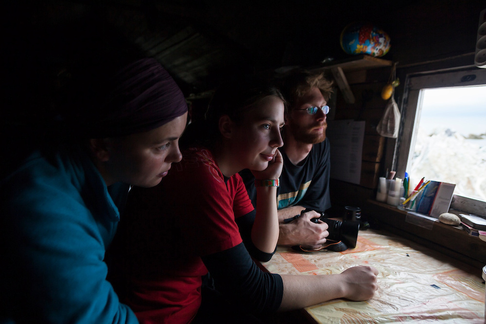 University students gaze out the window of the small Polish research station in Hyttevika, Svalbard.