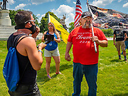 04 JULY 2020 - DES MOINES, IOWA: A member of Black Lives Matter (left) argues with Donald Trump supporters on the grounds of the Iowa State Capitol. Hundreds of people came to the grounds of the Iowa State Capitol to protest against and in favor of historic monuments on the capitol grounds. Several hundred people protested against a monument to Christopher Columbus and the stereotypical depiction of Native Americans on the capitol grounds. About 50 people came to the capitol to rally in support of the monuments. The protest against the monuments was organized by Seeding Sovereignty, a collective of indigenous women. The rally to defend the monuments was organized by an Iowa chapter of Three Percenters.     PHOTO BY JACK KURTZ