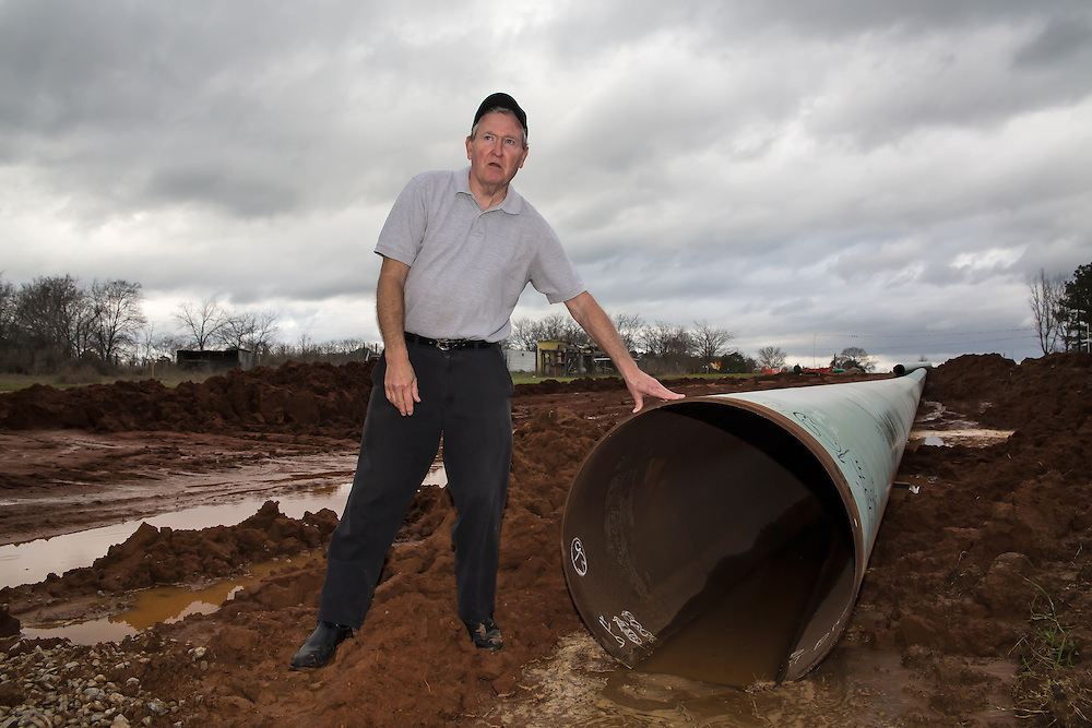 Douglas, Texas, February 19, Mike Bishop stands in front of a section of the Keystone XL pipeline being installed on his property.