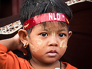 09 NOVEMBER 2015 - YANGON, MYANMAR: A child at NLD headquarters Monday afternoon. Thousands of National League for Democracy (NLD) supporters gathered at NLD headquarters on Shwegondaing Road in central Yangon to celebrate their apparent landslide victory in Myanmar's national elections that took place Sunday. The announcement of official results was delayed repeatedly Monday, but early reports are that the NLD did very well against the incumbent USDP.     PHOTO BY JACK KURTZ