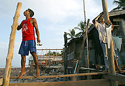 Koh Lanta, Thailand--Two men work on rebuilding a house after a Tsunami destroyed it in the village of Hua Laem on Koh Lanta island, Thailand. Despite the fact that the Thai government is threatening to move the village to another location away from the ocean, many of the  villagers are repairing or rebuilding their original homes.  01/18/05 <br />© Julia Cumes / The Image Works