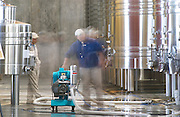 View over the winery, stainless steel fermentation tanks. Winery workers with a pump pumping from one tank to another. Bodega NQN Winery, Vinedos de la Patagonia, Neuquen, Patagonia, Argentina, South America