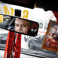 Buenos Aires, Argentina 04 September 2009<br /> A taxi driver is reflected in his car's mirror, decorated with Catholics symbols and popular Argentinians myths.<br /> PHOTO: EZEQUIEL SCAGNETTI