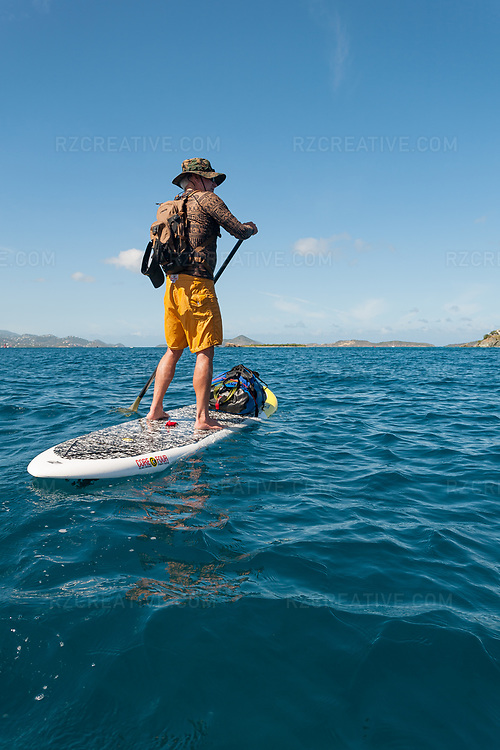 Standup paddler Ted Rutherford paddles around Contant Point on the island of St. John in the U.S. Virgin Islands. © Robert Zaleski / rzcreative.com<br /> —<br /> To license this image contact: robert@rzcreative.com