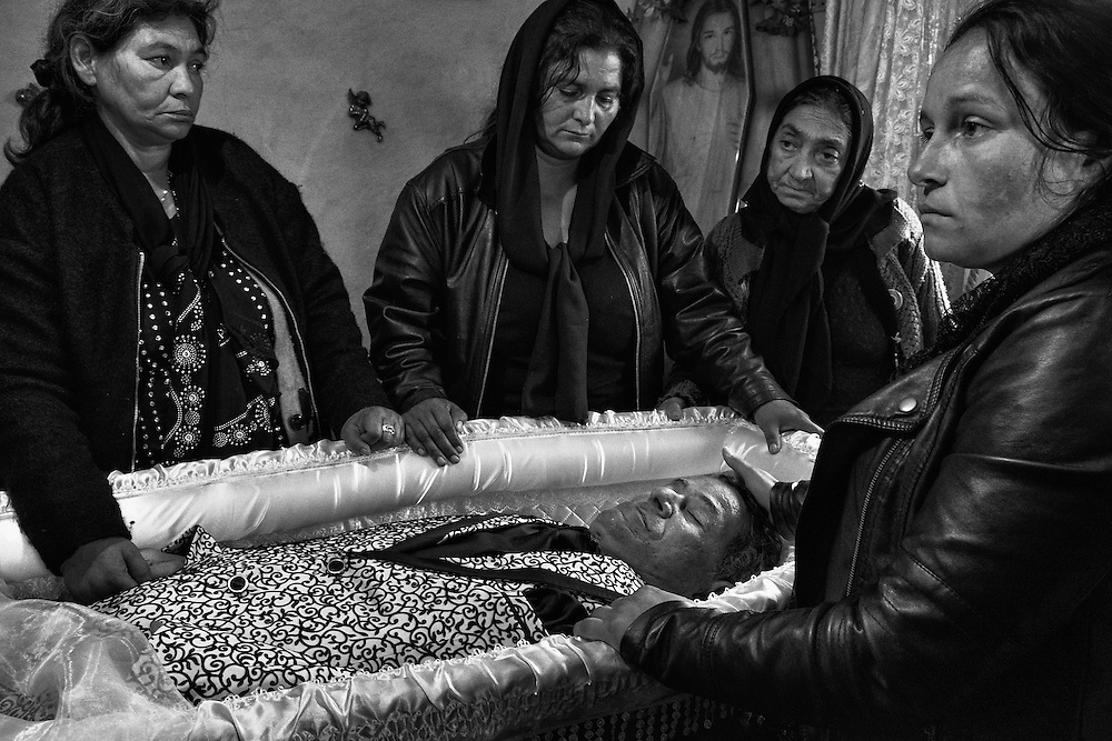 Close female realtives of a decased Roma man grieve beside his open coffin during a wake in the village of Valea Seaca in Bacau County, Romania.