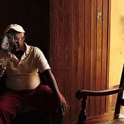 Man smoking a cigar inside his house in Trinidad.