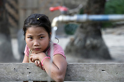 Bat 10 yrs old hangs around tap stand playing with her friends. SCI has installed a gravity flow water system here. Children often collect water for the family, and originally would have had to go down to the river with heavy buckets. Naluang Village, Nambac District, Luang Prabang Province. Lao PDR