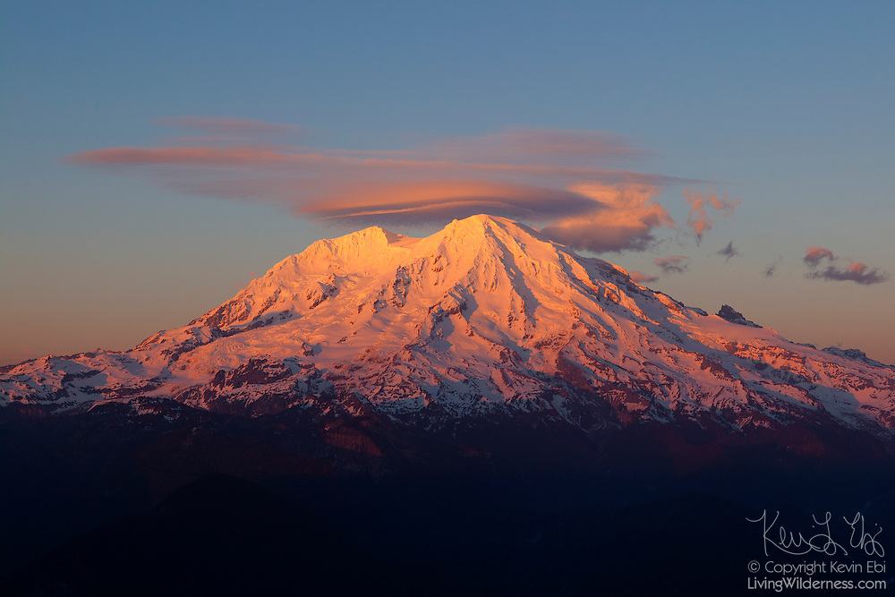 A lenticular cloud hovers over the summit of Mount Rainier at sunset. Mount Rainier, at 14411 feet (4392 meters), is the tallest peak in Washington and the highest summit in the Cascade mountain range. This view of Mount Rainier's southwestern face was captured from the summit of High Rock.
