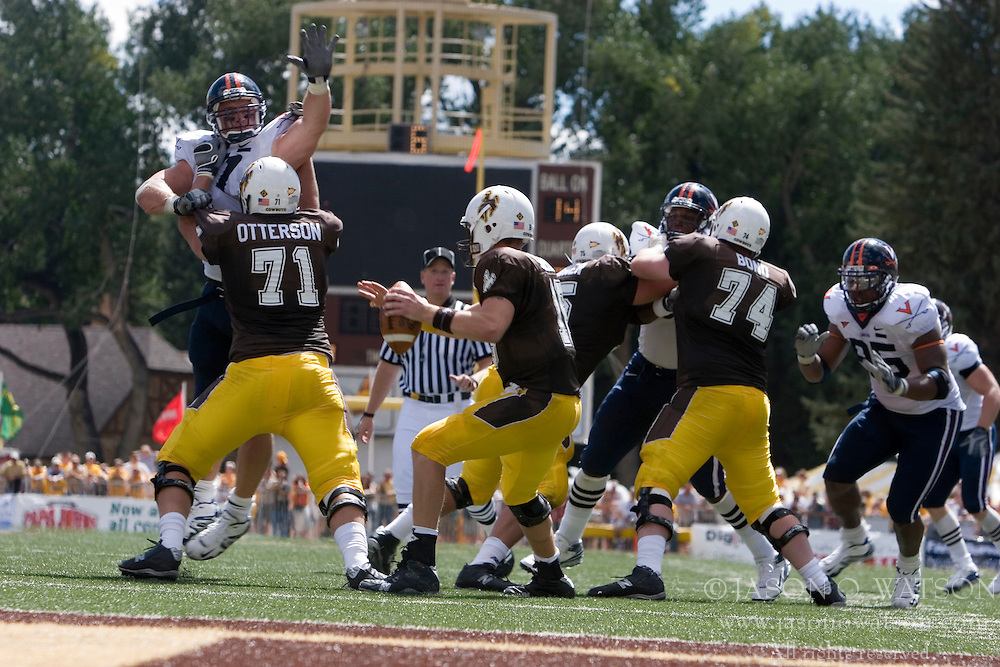 Virginia defensive end Chris Long (91) leaps over Wyoming tackle Ryan Otterson (71) to put pressure on Wyoming quarterback Karsten Sween (16).  The Wyoming Cowboys defeated the Virginia Cavaliers 23-3 at War Memorial Stadium in Laramie, WY on September 1, 2007.