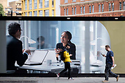 As two strangers walk towards each other while distracted by their phones, work colleagues appear on a corporate billboard making eye contact, in a face-to-face meeting of ideas in an office workplace, on 13th September 2021, in London, England.