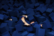 Annalee Wilson, 18, of Lyme struggles out of a pit of foam cubes after slipping off the bar while practicing maneuvers on a high bar at Northern Lights Gymnastics in Wilder, Vt., Monday, July 28, 2014.<br /> (Valley News - James M. Patterson)
