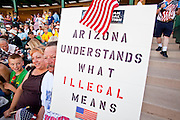 """May 29 - TEMPE, AZ: Opponents of illegal immigration at a rally organized by the Tea Party in Tempe, AZ, Saturday. About 3,000 people attended a """"Buy Cott Arizona"""" rally at Tempe Diablo Stadium in Tempe, AZ Saturday night. The rally was organized by members of the Arizona Tea Party movement to show support for Arizona law SB1070. The """"Buy Cott"""" is a reaction to the economic boycott planned by opponents of SB1070. SB1070 makes it an Arizona state crime to be in the US illegally and requires that immigrants carry papers with them at all times and present to law enforcement when asked to. Critics of the law say it will lead to racial profiling, harassment of Hispanics and usurps the federal role in immigration enforcement. Supporters of the law say it merely brings Arizona law into line with existing federal laws. Photo by Jack Kurtz"""
