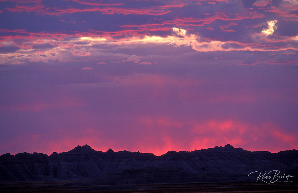 Fiery clouds at sunset over silhouetted rock formations in the badlands, Badlands National Park, South Dakota USA