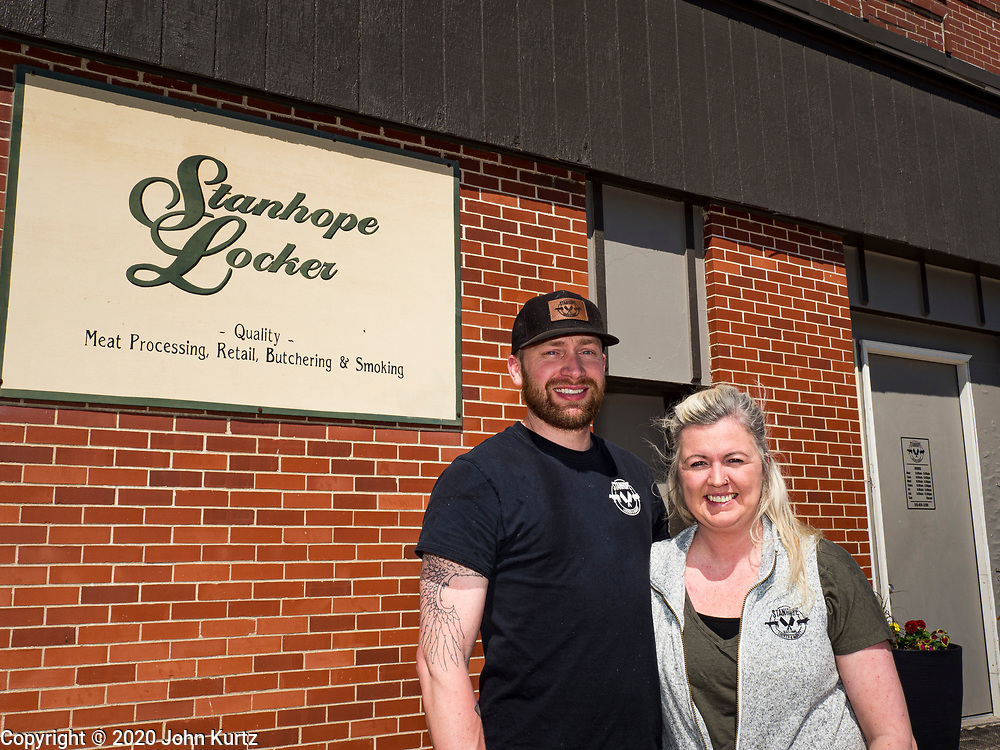 30 APRIL 2020 - STANHOPE, IOWA: WES ZANKER, and his wife, SHAUNNA ZANKER owners of Stanhope Locker and Market, in Stanhope, Iowa, in front of their store. The family owned meat locker slaughters and butchers beef cattle, pigs, and sheep. The COVID-19 (SARS-CoV-2/Coronavirus) pandemic has spread among employees in the meat packing plants in the Iowa, Nebraska, South Dakota, and Minnesota, forcing many to close or curtail operations. This has resulted in farmers euthanizing thousands of pigs and beef cattle. Pork production has been slashed by about 40% because of the pandemic. Meat lockers and family owned butchering facilities have been swamped with farmers and ranchers trying to sell their livestock to them rather than the meat packing plants, but the meat lockers are backed up by the huge increase in supply. Many meat lockers are now full through the end of the year. Stanhope Locker and Market doesn't have any openings for slaughtering and butchering either cattle or pigs until mid-December 2020.        PHOTO BY JACK KURTZ