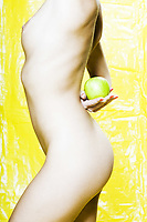 caucasian woman naked holding an apple studio yellow background