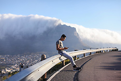 January 25, 2019 - Young male runner sitting on rural road barrier looking at smartphone, Cape Town, Western Cape, South Africa (Credit Image: © Cultura via ZUMA Press)