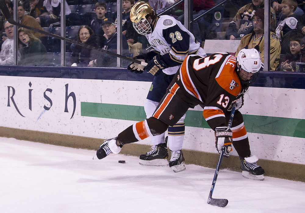 March 15, 2013:  Bowling Green forward Adam Berkle (13) and Notre Dame defenseman Stephen Johns (28) battle for the puck during NCAA Hockey game action between the Notre Dame Fighting Irish and the Bowling Green Falcons at Compton Family Ice Arena in South Bend, Indiana.  Notre Dame defeated Bowling Green 1-0 in overtime.