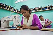 A Nepalese female factory worker sits at a sewing machine in the Surijha Traders garment factory in Kathmandu, Nepal.  The garments produced in the factory are exported around the world. The factory works closely with the Friends of Needy Children organization in providing fair employment opportunities for young Nepalese men and women.