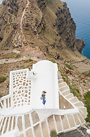 Aerial view woman lying on roof on Santorini traditional house with sea in background, Greece.