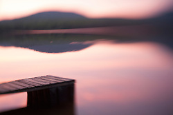 United States, New Hampshire, Lyme, dock and reflection of mountain in Hinman Pond at sunset