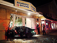 Waterbury, Conn. 04 Oct. 2006: Waterbury police officers inspect the scene of an accident in which a driver crashed into an Academy of Driving building. The accident happened while the driver was speeding during a joy-ride in a stolen vehicle...Josalee Thrift Photo