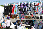 Racks of traditional Hmong costume dresses at festival booth. Hmong Sports Festival McMurray Field St Paul Minnesota USA