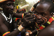 A Hamar man's face is painted before taking part in a bull jump, in South Omo, Ethiopia. The bull jump is a ritual at which a man runs across the backs of a row of bullocks in order to become eligible for marriage. The 40,000-strong, cattle-herding Hamar are among the largest of the 20 or so ethnic groups which inhabit the culturally diverse Omo region in south-west Ethiopia.