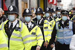 © Licensed to London News Pictures. 17/10/2020. London, UK. Police in face masks follow protestors calling for an end to Coronavirus lockdown restrictions marching on Oxford Street in central London. Other groups who believe that the virus is a hoax and a conspiracy have also joined today's demonstration called the ' March for Freedom'. Photo credit: Peter Macdiarmid/LNP
