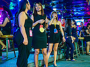 "03 NOVEMBER 2016 - BANGKOK, THAILAND: Women wearing a black mourning clothes working on ""Soi Cowboy,"" one of Bangkok's best known ""adult entertainment districts."" Bangkok's infamous nightlife has been scaled back during the mourning period for the late Bhumibol Adulyadej, King of Thailand. The revered King died on 13 October 2016 at age 88. The government declared a year of mourning. The government ordered Thailand's notorious adult entertainment districts to turn off their neon lights, dress employees in black and ensure that music can't be heard on the street in front of the venues for 30 days, the government said the entertainment venues could resume normal operations on 14 November.        PHOTO BY JACK KURTZ"