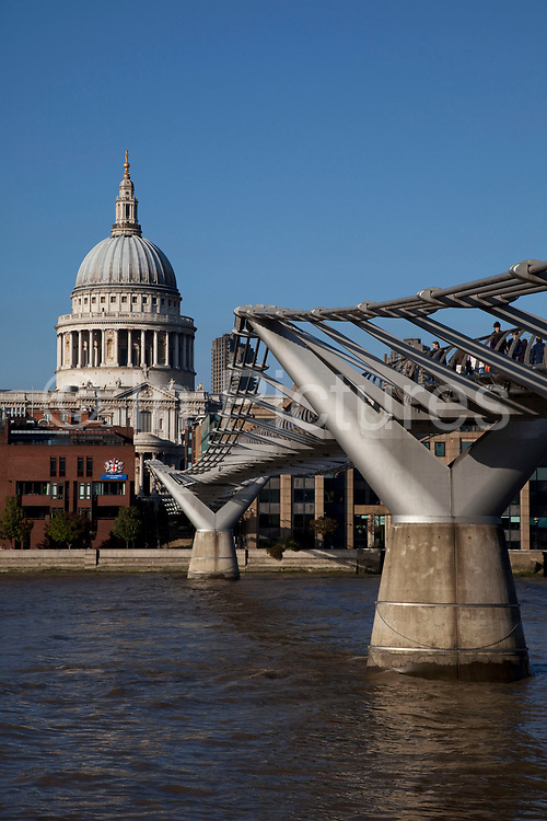 View of tourists and local people crossing the Millennium Bridge with St Pauls Cathedral rising in the background, London. Londoners nicknamed the bridge the Wobbly Bridge after people felt an unexpected swaying motion on the first two days after the bridge opened. The bridge was closed later that day, and was closed for almost two years while modifications were made to eliminate the sway entirely.