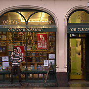 Man reading in front of Quinto Bookshop, rare and antique books dealers, London