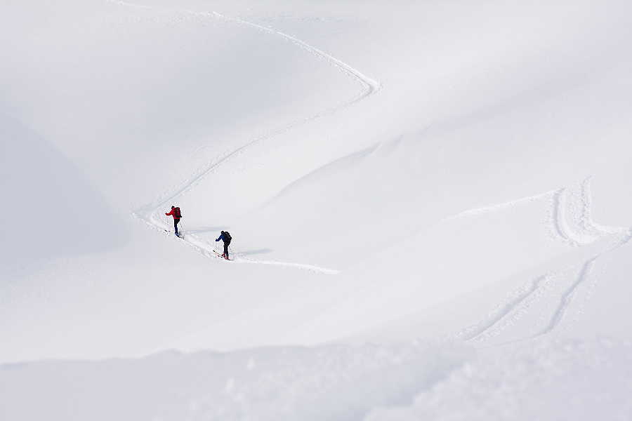 A pair of skiers follow ski tracks in the Mount Baker backcountry along the classic ski tour around Table Mountain, Mount Baker-Snoqualmie National Forest, Washington.