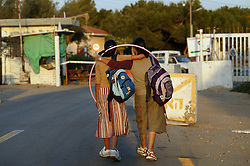 Two teenage girls approach the checkpoint outside the Nezer Hazani settlement in Gaza, Palestinian Territories, Nov. 6, 2004. Israel's parliament recently supported compensation payments for Jewish settlers leaving the Gaza Strip in a vital vote for Prime Minister Ariel Sharon's plan to evacuate the occupied territory.