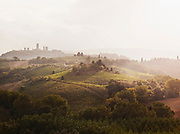 The rolling hills of Tuscany at sunset, with the town of San Gimignano distinct in the distance, Italy