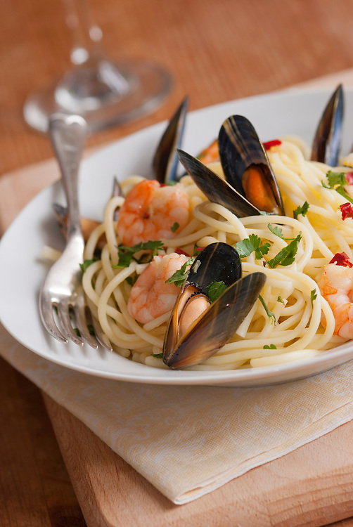 Spaghetti with king prawns, mussels and herbs on a plate