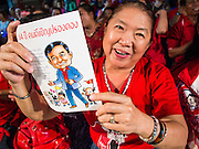 27 JULY 2013 - BANGKOK, THAILAND: Thai Red Shirts hold up their birthday cards for Thaksin Shinawatra during their birthday party for Thaksin. The Red Shirts celebrated former Prime Minister Thaksin Shinawatra's 64th birthday with a party at Phibun Prachasan School in Bangkok. They had a Buddhist Merit Making Ceremony, dinner, cake and entertainment. Most of the Red Shirt political elite traveled to Hong Kong for a party with Thaksin. Thaksin, the former Prime Minister, was deposed by a coup in 2006 and subsequently convicted of corruption related crimes. He went into exile rather than go to jail but remains very popular in rural parts of Thailand. His sister, Yingluck Shinawatra is the current Prime Minister and was elected based on her brother's recommendation.     PHOTO BY JACK KURTZ