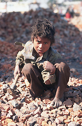 Young boy using hammer to break bricks to be used to mend roads,