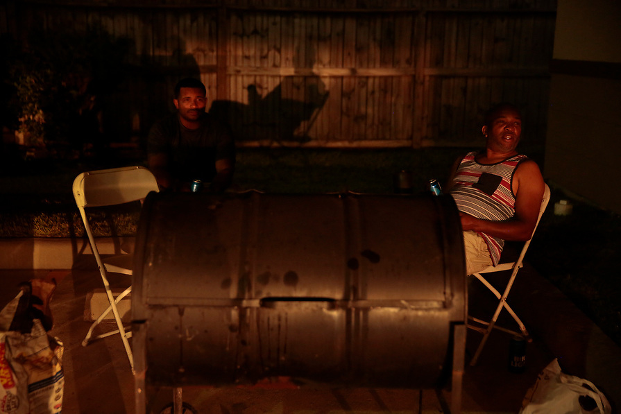 """Dameon Horton, (L) and his father Paul Horton grill ribs outside their FEMA provided hotel room in the aftermath of tropical storm Harvey in Houston, Texas, U.S. September 10, 2017. Talking about the the flooding, Paul said, """"I didn't know what to do, but I couldn't crack under pressure, I got kids, I had to go into survival mode. Texas is strong, for real, we gonna get ourselves together and get back to work."""""""