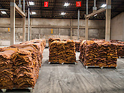 """16 DECEMBER 2014 - CHUM SAENG, RAYONG, THAILAND: Smoked rubber sheets in a warehouse on a large rubber plantation near Chum Saeng, Thailand. Thailand is the second leading rubber exporter in the world. In the last two years, the price paid to rubber farmers has plunged from approximately 190 Baht per kilo (about $6.10 US) to 45 Baht per kilo (about $1.20 US). It costs about 65 Baht per kilo to produce rubber ($2.05 US). Prices have plunged 5 percent since September, when rubber was about 52Baht per kilo. Some rubber farmers have taken jobs in the construction trade or in Bangkok to provide for their families during the slump. The Thai government recently announced a """"Rubber Fund"""" to assist small farm owners but said prices won't rebound until production is cut and world demand for rubber picks up.    PHOTO BY JACK KURTZ"""