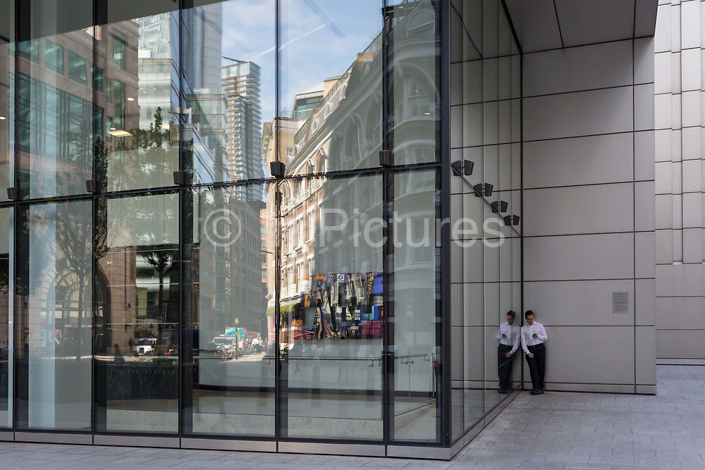 A businessman stands outside the UBS bank to make a call on Sun Street in the City of London, the capitals financial district - aka the Square Mile, on 8th August, in London, England.
