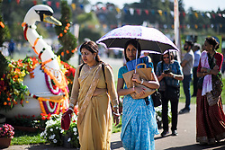 © Licensed to London News Pictures. 02/09/2018. Aldenham, UK. A woman shelters form the sun, underneath an umbrella, during Janmashtami Hindu festival at Bhaktivedanta Manor Hare Krishna Temple in Aldenham, Hertfordshire. Janmashtami is an annual Hindu festival that celebrates the birth of Krishna. Bhaktivedanta Manor, the venue fo the event, was donated to the Hare Krishna movement in February 1973 by former Beatle George Harrison. Photo credit: Ben Cawthra/LNP