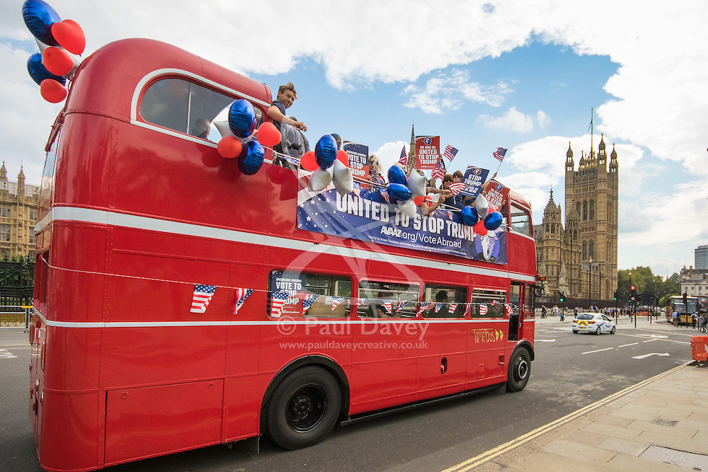 """London, September 21st 2016. A """"Stop Trump"""" open topped red London double-decker bus passes the Houses of Parliament and Big Ben in London in a bid to encourage US expats to register to vote in the Presidential election, expecting the majority of them to be more inclined to support Hilary Clinton."""