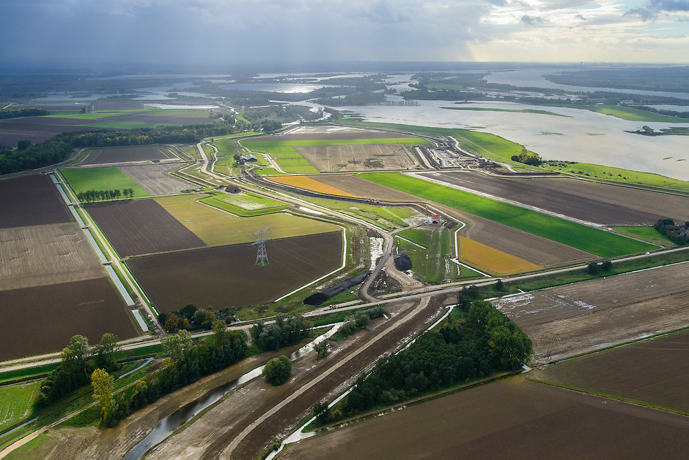 Nederland, Noord-Brabant, Werkendam, 23-10-2013; Ruimte voor de Rivier project Ontpoldering Noordwaard. Het deel rechtsboven is reeds ontpolderd, onder het gedeelte in ontwikkeling waar boerderijen en particuliere huizen op nieuw opgeworpen terpen gebouwd worden. Midden in beeld een nieuwe dijk, hierlangs zal het water stromen, vanaf rivier de Nieuwe Merwede , de bestaande dijk krijgt een instroomopening.<br /> Delen van de polder (links) wordt ontpolderd en de dijken worden verlegd en/of verlaagd waardoor bij hoogwater het rivierwater ook door de polder sneller weg kan stromen richting zee. Gevolg van de ingrepen is ook dat de waterstand verder stroomopwaarts zal dalen.<br /> National Project Ruimte voor de Rivier (Room for the River) By lowering and / or moving the dike of the Noordwaard polder the area will become subject to controlled inundation and function as a dedicated water detention district. Houses and farmhouses will be constructed on new dwelling mounds. The polder is partly depoldered.<br /> luchtfoto (toeslag op standard tarieven);<br /> aerial photo (additional fee required);<br /> copyright foto/photo Siebe Swart