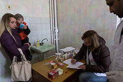 Olga Malishenko, 23, with her son Vladislav, 2yrs 7 months, receive their prescribed medicines from the MSF pharmacy set up in the mobile clinic being held at the Bolshaya Vergunka polyclinic in a suburb of Lugansk.