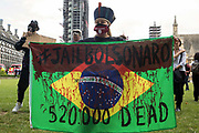A woman holds a Brazilian flag painted with text criticising President Jair Bolsonaros handling of the Covid-19 pandemic in Brazil during a protest in Parliament Square by members of the Brazilian community on 3rd July 2021 in London, United Kingdom. Tens of thousands of people also demonstrated across Brazil to call for the impeachment of the president following more than half a million coronavirus deaths there and allegations that members of his government may have illegally profited from the purchase of Covid-19 vaccines.