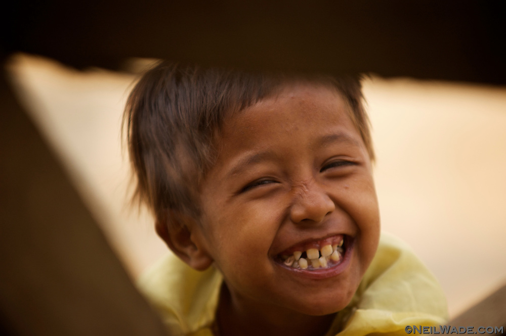 This cute Burmese girl was happy to have her portrait taken through some pallets in Mandalay, Myanmar (Burma)