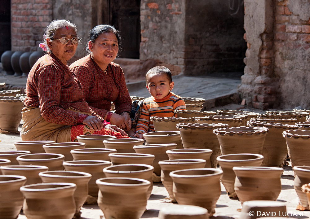 Two women and a boy sitting in the middle of the pottery in Thimi. Madhyapur Thimi is famous for its pottery production.